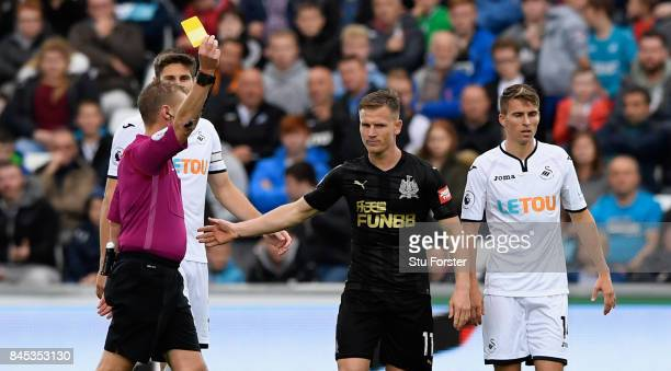 Newcastle player Matt Ritchie receives a yellow card from referee Michael Jones during the Premier League match between Swansea City and Newcastle...