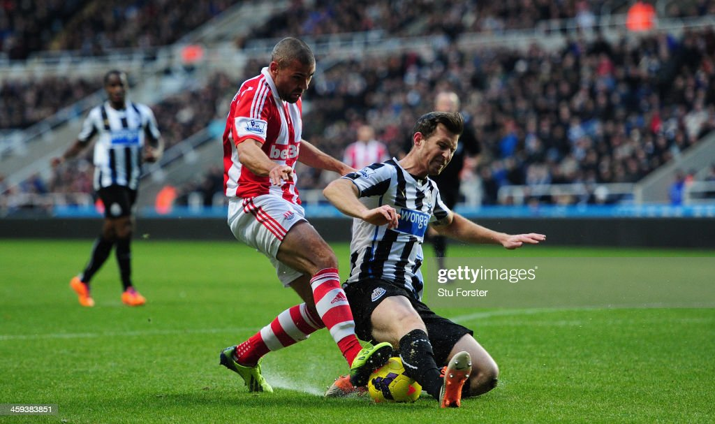 Newcastle player Mike Williamson (r) challenges Jonathan Walters during the Barclays Premier League match between Newcastle United and Stoke City at St James' Park on December 26, 2013 in Newcastle upon Tyne, England.