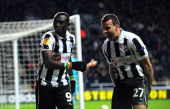 Newcastle players Papiss Cisse and Steven Taylor celebrate the winning goal during the UEFA Europa League Round of 16 second leg match between...