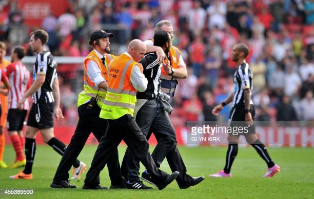 A Newcastle United fan is lead away at the end of the match after running onto the pitch during the English Premier League football match between...