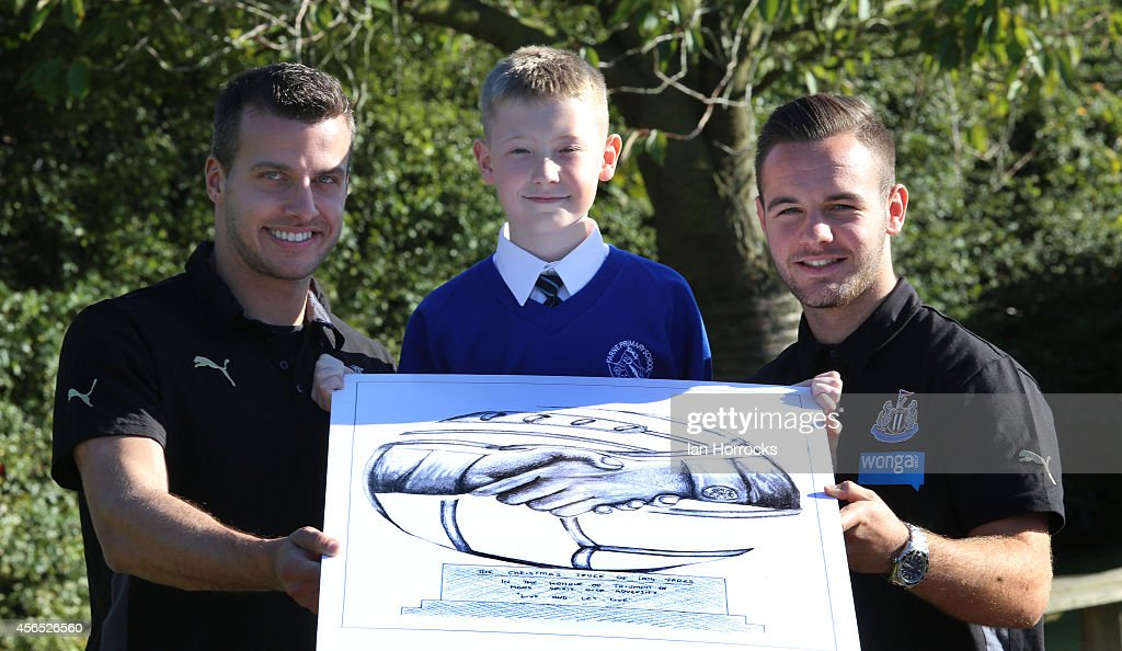 Newcastle United players Steven Taylor (L) and Adam Armstrong (R) with competition winner Spencer Turner (C) during a visit to Farne Primary School as part of the Football Remembers Memorial Competition on October 02, 2014 in Newcastle upon Tyne, England.