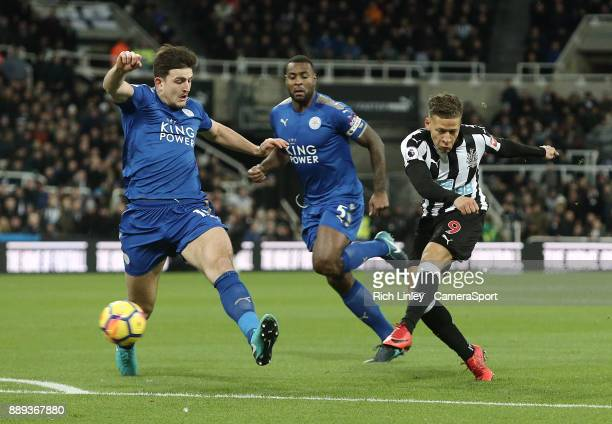 Newcastle United's Dwight Gayle shoots despite the attentions of Leicester City's Harry Maguire during the Premier League match between Newcastle...
