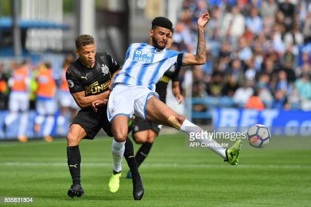 Newcastle United's English forward Dwight Gayle vies with Huddersfield Town's Danish midfielder Philip Billing during the English Premier League...