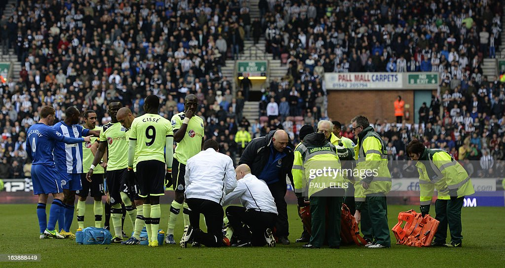 """Newcastle United's French defender Massadio Haidara receives attention on the pitch before being stretchered off the pitch after being injured in a tackle by Wigan Athletic's English striker Callum McManaman during the English Premier League football match between Wigan Athletic and Newcastle United at The DW Stadium in Wigan, north-west England, on March 17, 2013. Haidara was stretchered off the pitch after the challenge that was unseen by referee Mark Halsey. USE. No use with unauthorized audio, video, data, fixture lists, club/league logos or """"live"""" services. Online in-match use limited to 45 images, no video emulation. No use in betting, games or single club/league/player publications"""