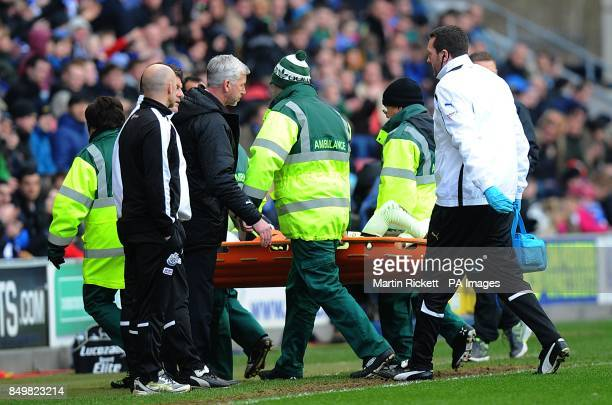 Newcastle United's Massadio Haidara is carried from the field on a stretcher after picking up an injury as manager Alan Pardew checks on his condition
