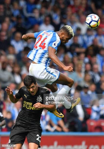 Newcastle United's Spanish midfielder Mikel Merino vies with Huddersfield Town's Beninese striker Steve Mounie during the English Premier League...