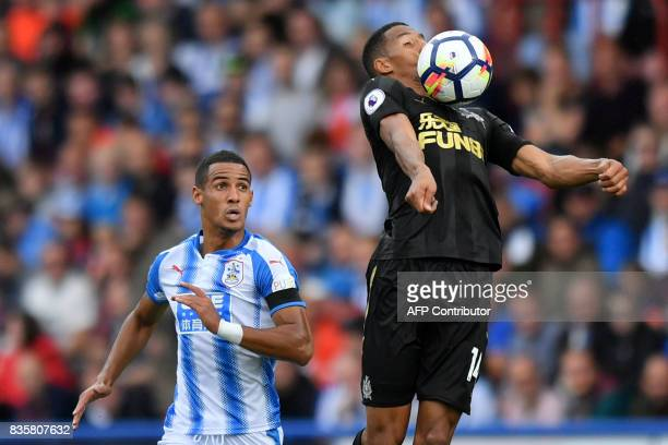 TOPSHOT Newcastle United's Spanish striker Ayoze Perez wins the header from Huddersfield Town's English midfielder Tom Ince during the English...