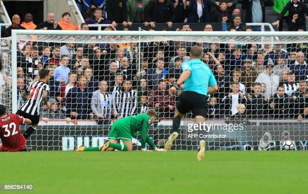 Newcastle United's Spanish striker Mato Joselu watches his attempt beat Liverpool's Belgian goalkeeper Simon Mignolet for Newcastle's first goal of...