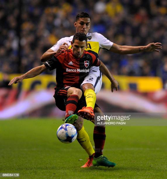Newell's Old Boys midfielder Maximiliano Rodriguez vies for the ball with Boca Juniors' defender Fernando Tobio during their Argentina First Divsion...