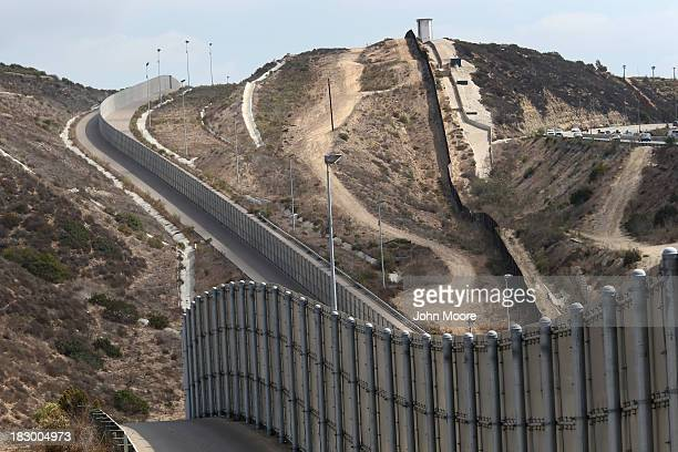 Newer and older sections of the USMexico border fence climb a hill on October 3 2013 near San Diego California While hundreds of thousands of...