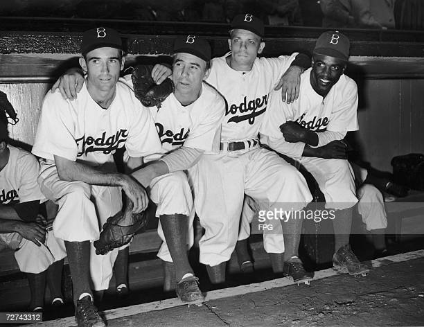 Newest Brooklyn Dodgers recruit Jackie Robinson on the end of the bench with his team mates at Ebbet's Field 1947 Robinson was the first African...