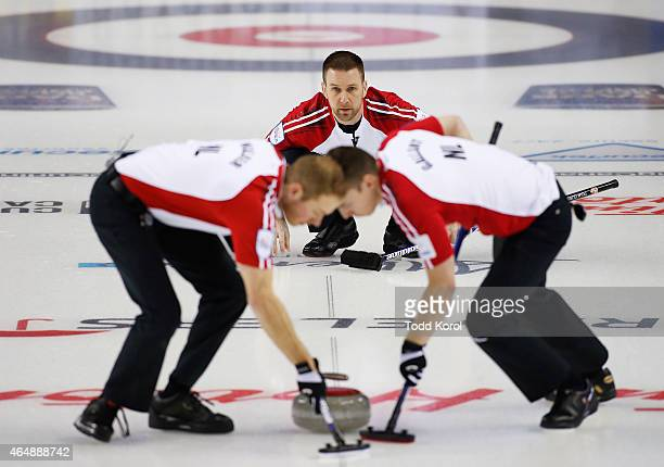 Newfoundland and Labrador skip Brad Gushue watches his shot with teammates lead Geoff Walker and second Brett Gallant in their game against Team...