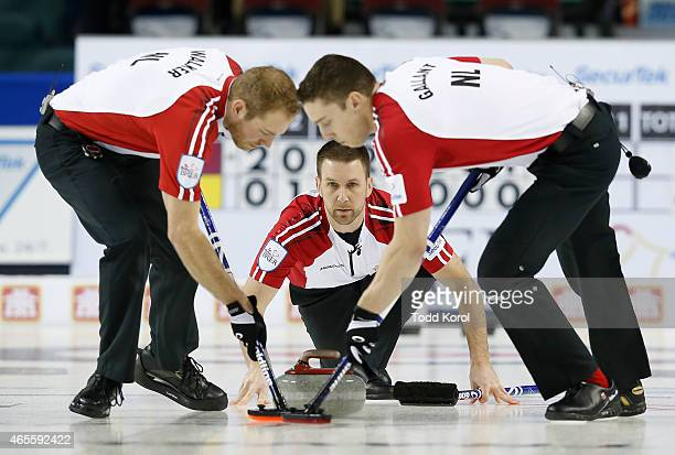 Newfoundland and Labrador skip Brad Gushue watches his shot with teammates lead Geoff Walker and second Brett Gallant in the bronze medal game they...