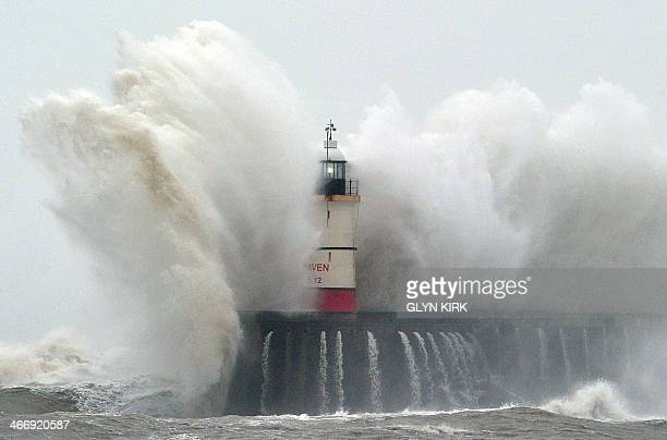 Newhaven Lighthouse is battered by waves during stormy weather in Newhaven on the southern coast of England on February 5 2014 More than 8000 homes...