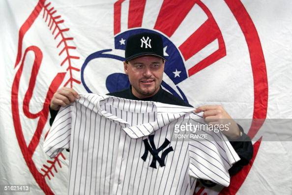 Newly acquired New York Yankees pitcher Roger Clemens holds up his new uniform during a press conference at spring training camp at Legends Field 20...