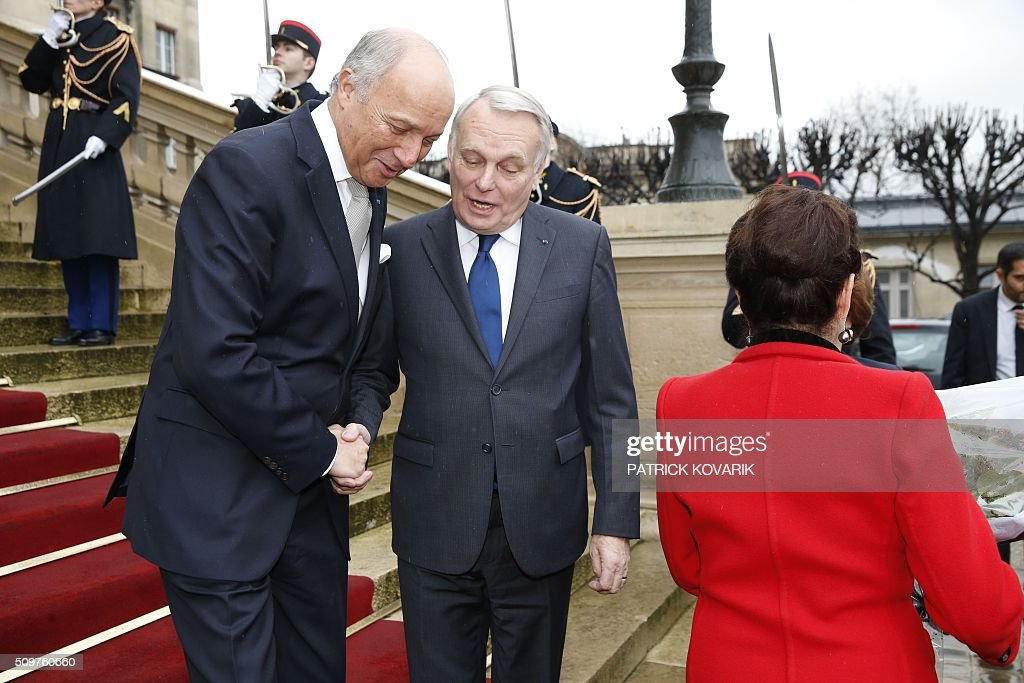 Newly appointed French Foreign Minister Jean-Marc Ayrault (C) escorts France's outgoing Foreign Minister Laurent Fabius (L) following the handover ceremony at the Foreign Ministry on February 12, 2016 in Paris. French President Francois Hollande reshuffled his cabinet on February 11, 2016, naming Jean-Marc Ayrault foreign minister and adding several ecologists to government as he seeks to widen his political base ahead of a presidential poll in 2017. / AFP / PATRICK KOVARIK
