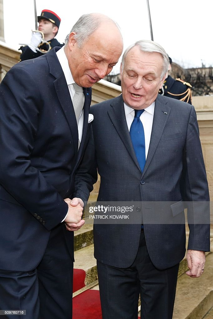 Newly appointed French Foreign Minister Jean-Marc Ayrault (R) escorts France's outgoing Foreign Minister Laurent Fabius following the handover ceremony at the Foreign Ministry on February 12, 2016 in Paris. French President Francois Hollande reshuffled his cabinet on February 11, 2016, naming Jean-Marc Ayrault foreign minister and adding several ecologists to government as he seeks to widen his political base ahead of a presidential poll in 2017. / AFP / PATRICK KOVARIK / ALTERNATIVE CROP