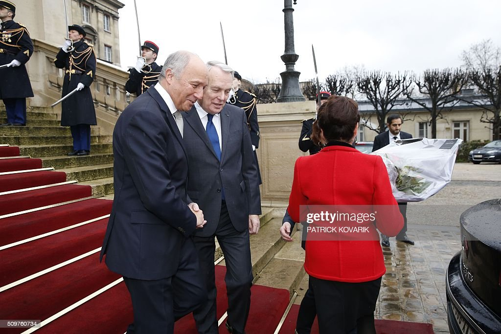 Newly appointed French Foreign Minister Jean-Marc Ayrault (2nd L) escorts France's outgoing Foreign Minister Laurent Fabius (L) following the handover ceremony at the Foreign Ministry on February 12, 2016 in Paris. French President Francois Hollande reshuffled his cabinet on February 11, 2016, naming Jean-Marc Ayrault foreign minister and adding several ecologists to government as he seeks to widen his political base ahead of a presidential poll in 2017. / AFP / PATRICK KOVARIK