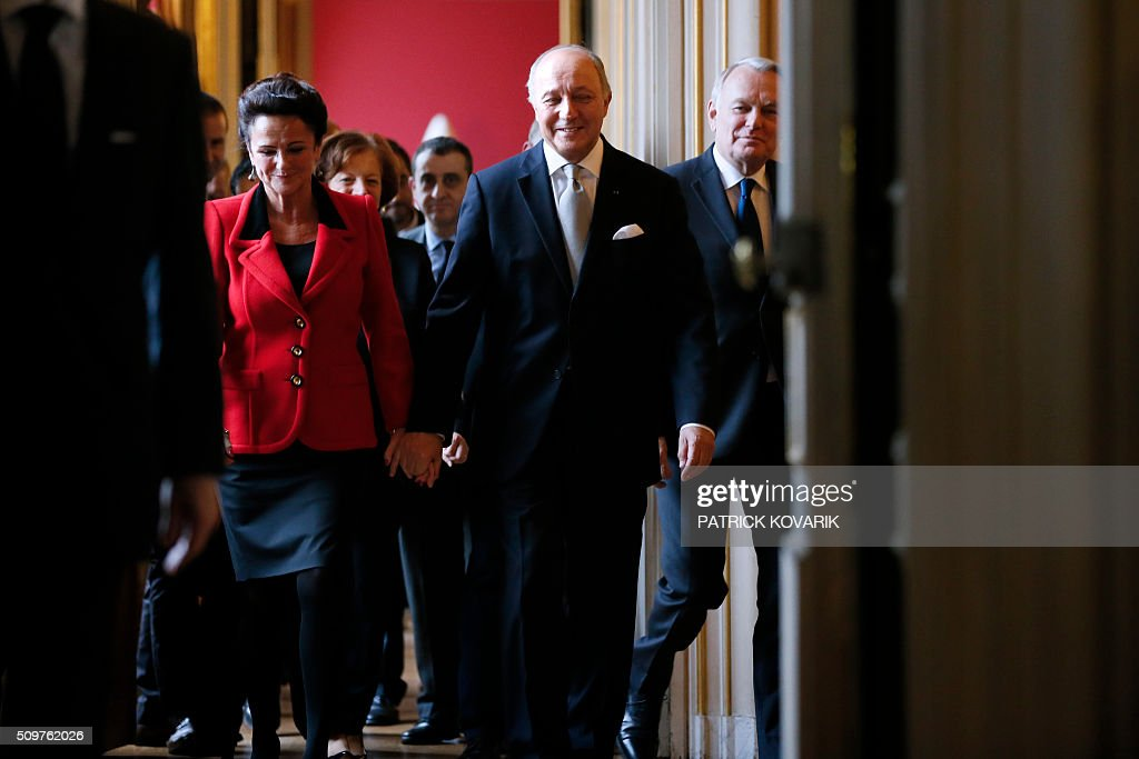 Newly appointed French Foreign Minister Jean-Marc Ayrault (R) escorts France's outgoing Foreign Minister Laurent Fabius (C) and his companion Marie-France Marchand-Baylet following the handover ceremony at the Foreign Ministry on February 12, 2016 in Paris. French President Francois Hollande reshuffled his cabinet on February 11, 2016, naming Jean-Marc Ayrault foreign minister and adding several ecologists to government as he seeks to widen his political base ahead of a presidential poll in 2017. / AFP / PATRICK KOVARIK