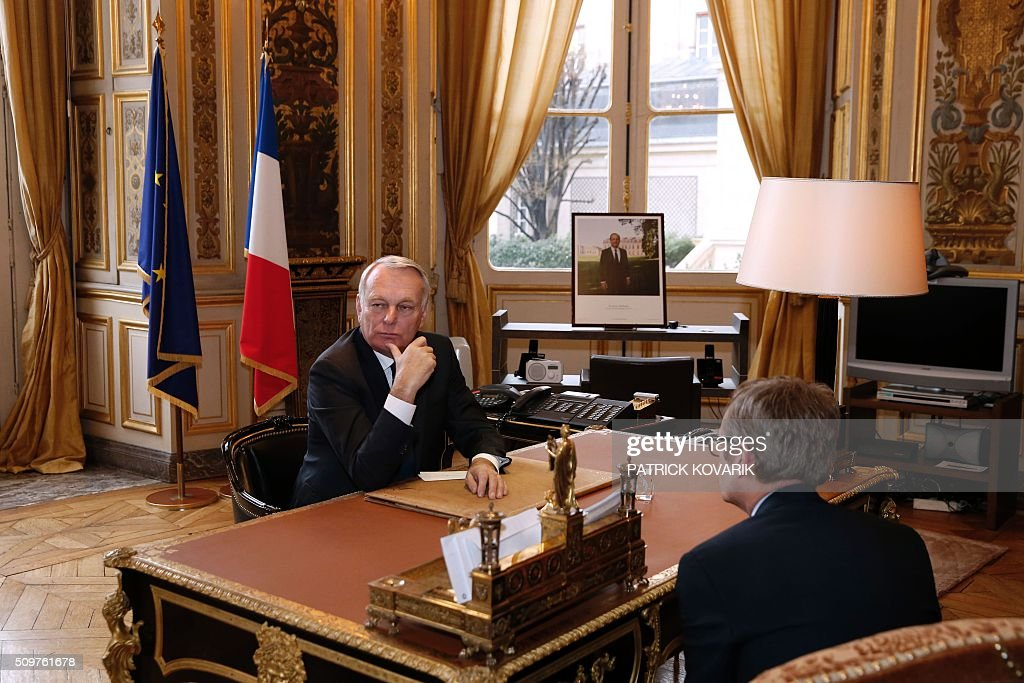 Newly appointed French Foreign Minister Jean-Marc Ayrault (L) is pictured at his desk at the Foreign Ministry following the handover ceremony on February 12, 2016 in Paris. French President Francois Hollande reshuffled his cabinet on February 11, 2016, naming Jean-Marc Ayrault foreign minister and adding several ecologists to government as he seeks to widen his political base ahead of a presidential poll in 2017. / AFP / PATRICK KOVARIK