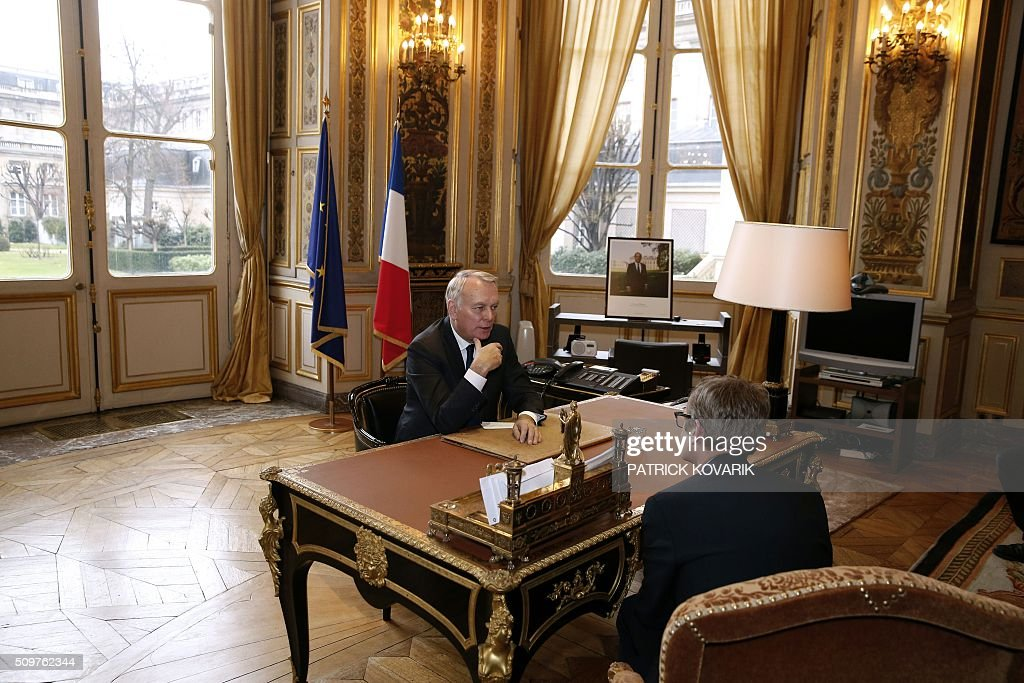 Newly appointed French Foreign Minister Jean-Marc Ayrault is pictured at his desk at the Foreign Ministry following the handover ceremony on February 12, 2016 in Paris. French President Francois Hollande reshuffled his cabinet on February 11, 2016, naming Jean-Marc Ayrault foreign minister and adding several ecologists to government as he seeks to widen his political base ahead of a presidential poll in 2017. / AFP / PATRICK KOVARIK