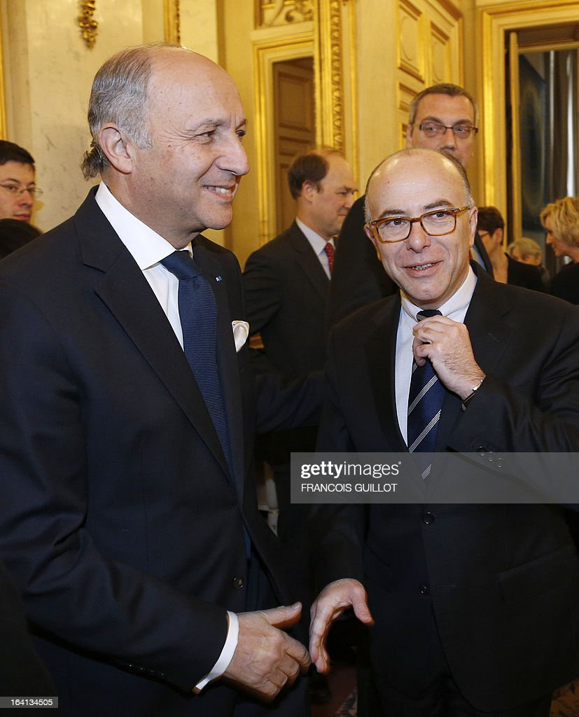 Newly appointed French Minister for Budget Bernard Cazeneuve (R ) shakes hand with French Minister of Foreign Affairs, Laurent Fabius, at the Quai d'Orsay Foreign ministry upon his arrival for a handing over ceremony in Paris on March 20, 2013. Cazenave was appointed yesterday Budget Minister to replace Jerome Cahuzac who resigned some hours earlier after prosecutors announced a probe into a Swiss bank account he allegedly used to hide assets from the tax authorities. Former Junior Minister for professional training Thierry Repentin replaced Cazeneuve as Minister for Europe.