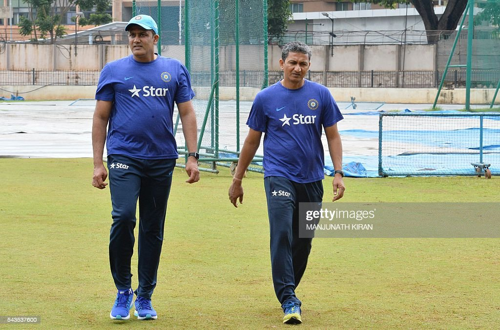 Newly appointed Indian cricket team head coach, Anil Kumble (L) and the team's batting coach Sanjay Bangar return after inspecting the ground at the National Cricket Academy (NCA) where the Indian cricket team is taking part in a preparatory camp before their West Indies tour, in Bangalore on June 29, 2016. / AFP / Manjunath Kiran