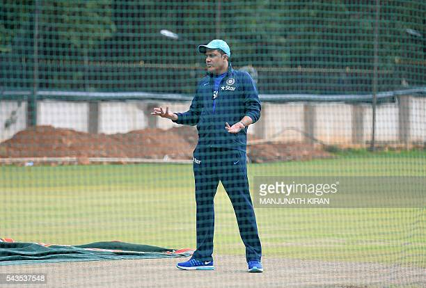 Newly appointed Indian cricket team head coach Anil Kumble talks to groundsmen at the nets of the National Cricket Academy where the Indian cricket...