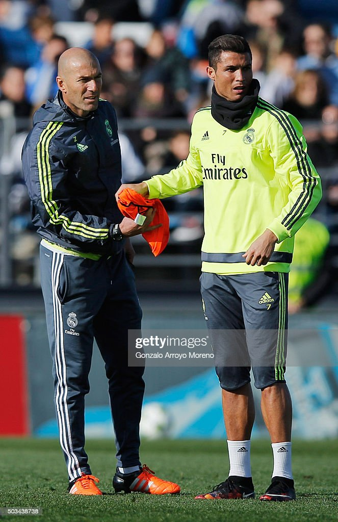 Newly appointed manager of Real Madrid Zinedine Zidane hands a bib to Cristiano Ronaldo during a Real Madrid training session at Valdebebas training ground on January 5, 2016 in Madrid, Spain.