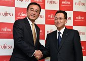 Newly appointed president of Japanese computer giant Fujitsu Tatsuya Tanaka shakes hands with outgoing president Masami Yamamoto at the company's...