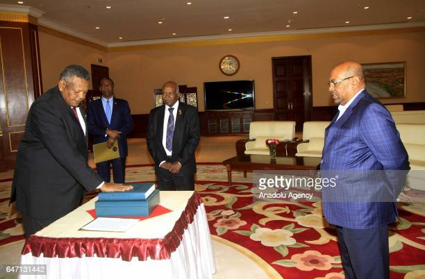 Newly appointed Sudanese Prime Minister Bakri Hassan Saleh swears during his oathtaking ceremony in front of Sudanese President Omar alBashir in...