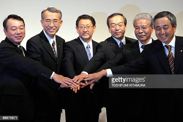 Newly appointed Toyota Motors President Akio Toyoda holds handinhand with his vice presidents Shinichi Sasaki Yukitoshi Funo Takeshi Uchiyamada...