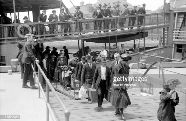 Newly arrived immigrants disembark from the passenger steamer Thomas C Millard upon their arrival at Ellis Island in New York early twentieth century