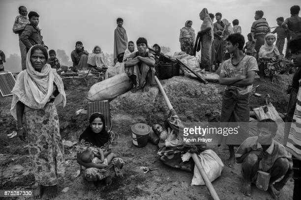 COX'S BAZAR BANGLADESH NOVEMBER 02 Newly arrived Rohingya Muslim refugees rest in the early morning as they sit on an earthen berm while waiting to...
