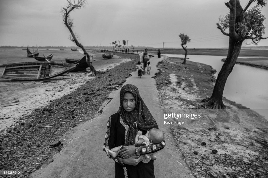 COX'S BAZAR, BANGLADESH - OCTOBER 29: A newly arrived Rohingya refugee woman carries her child as she walks on a broken road after arriving at Shah Porir Dwip on October 29, 2017 near Cox's Bazar, Bangladesh. More than 600,000 Rohingya refugees have flooded into Bangladesh to flee an offensive by Myanmar's military that the United Nations has called 'a textbook example of ethnic cleansing'. The refugee population continues to swell further, with thousands more Rohingya Muslims making the perilous journey on foot toward the border, or paying smugglers to take them across by water in wooden boats. Hundreds are known to have died trying to escape, and survivors arrive with horrifying accounts of villages burned, women raped, and scores killed in the 'clearance operations' by Myanmar's army and Buddhist mobs that were sparked by militant attacks on security posts in Rakhine state on August 25, 2017. What the Rohingya refugees flee to is a different kind of suffering in sprawling makeshift camps rife with fears of malnutrition, cholera, and other diseases. Aid organizations are struggling to keep pace with the scale of need and the staggering number of them - an estimated 60 percent - who are children arriving alone. Bangladesh, whose acceptance of the refugees has been praised by humanitarian officials for saving lives, has urged the creation of an internationally-recognized 'safe zone' where refugees can return, though Rohingya Muslims have long been persecuted in predominantly Buddhist Myanmar. World leaders are still debating how to confront the country and its de facto leader, Aung San Suu Kyi, a Nobel Peace Prize laureate who championed democracy, but now appears unable or unwilling to stop the army's brutal crackdown.