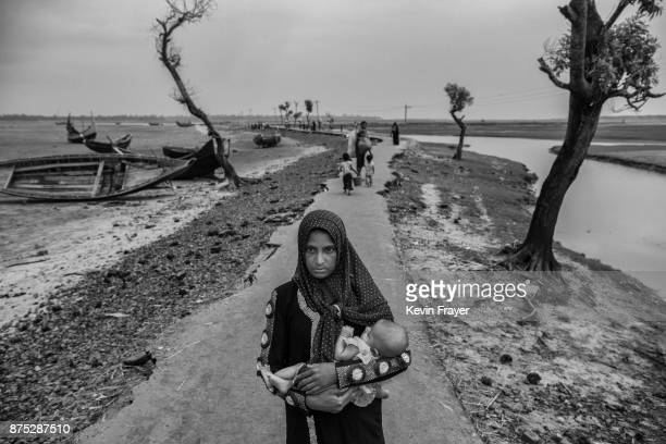COX'S BAZAR BANGLADESH OCTOBER 29 A newly arrived Rohingya refugee woman carries her child as she walks on a broken road after arriving at Shah Porir...