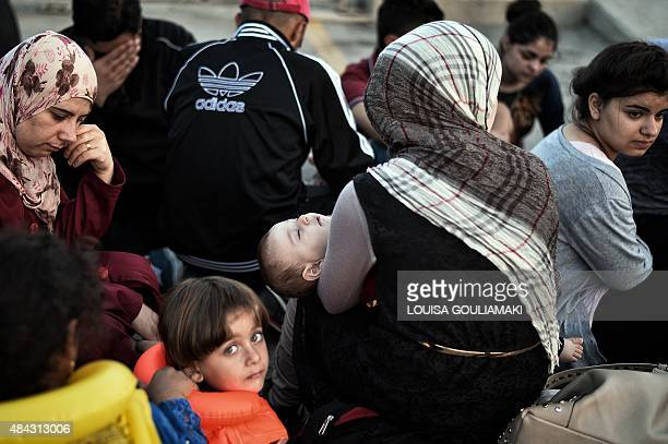 Newly arrived Syrian migrants wait in the port of Kos to be registered on the Eleftherios Venizelos liner on August 17 2015 Authorities on the island...