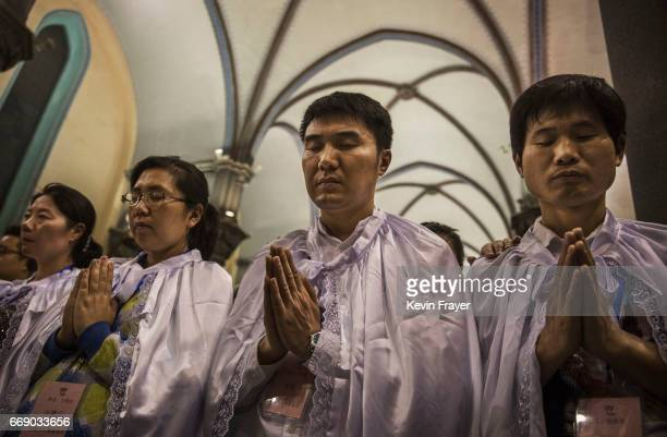 Newly baptized Chinese Catholic worshippers pray during a special ceremony at a mass on Holy Saturday during Easter celebrations at the government...