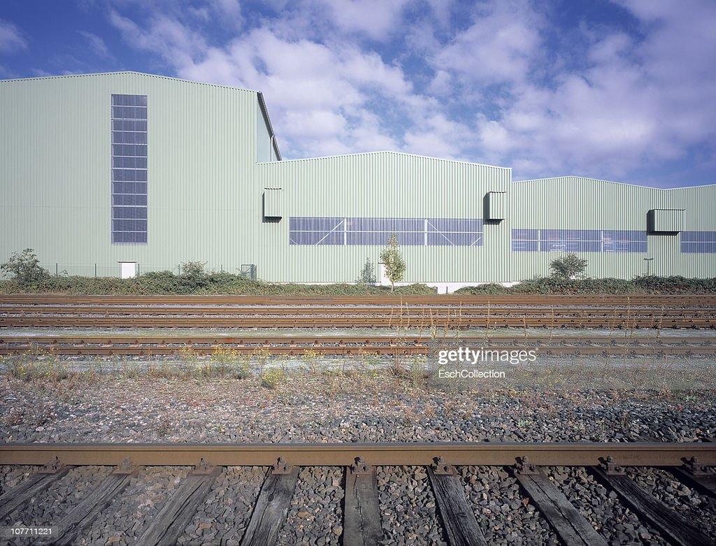 Newly built industrial building alongside railroad : Stock Photo