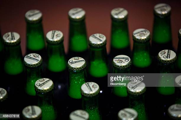 Newly capped bottles of Staropramen beer pass along the production line ahead of labeling at the Pivovary Staropramen AS brewing company operated by...