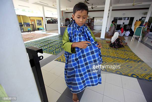 A newly circumcised boy walks after taking part in a mass circumcision ceremony in Kajang outside Kuala Lumpur on November 20 2011 About 30 boys aged...