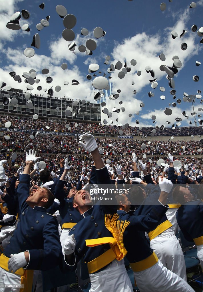 Newly commissioned 2nd lieutenants throw their caps in the air as a team of Air Force Thunderbirds fly over the 2011 graduating class of the US Air...