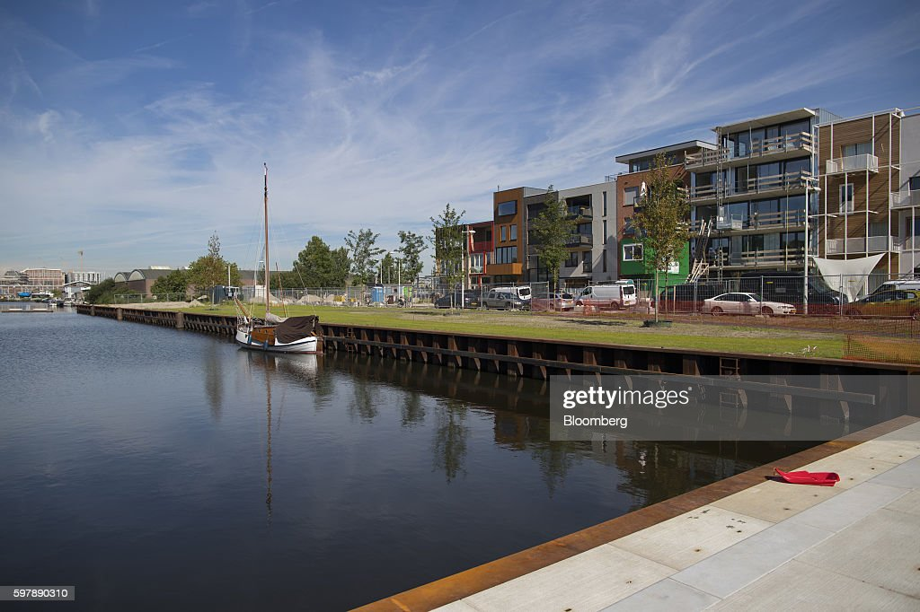 Newly constructed residential property stands beside green space and a waterway in the Noord district of Amsterdam Netherlands on Thursday Aug 25...