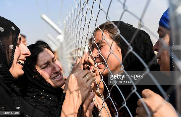 TOPSHOT Newly displaced Iraqi's who fled from the city of Mosul Iraq's last major Islamic State group stronghold are reunited with their relatives...
