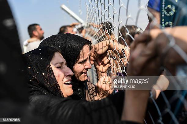 Newly displaced Iraqi's who fled from the city of Mosul Iraq's last major Islamic State group stronghold cry as they are reunited with their...