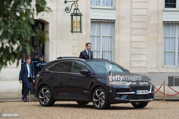 Newly elected French President Emmanuel Macron looks from the opened roof of a car has he arrives at the Elysee Palace after laying flowers at the...