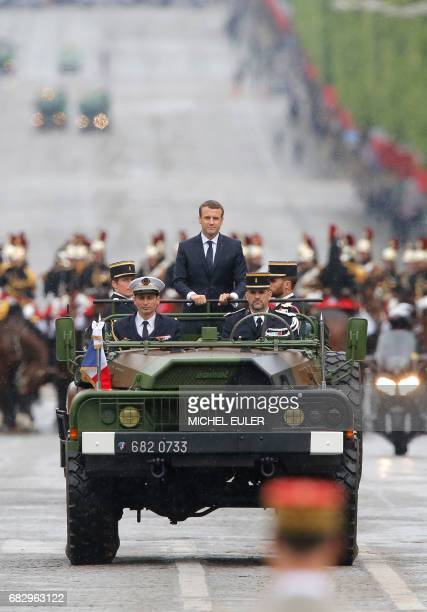 Newly elected French president Emmanuel Macron waves as he parades in a military car on the Champs Elysees avenue after his formal inauguration...