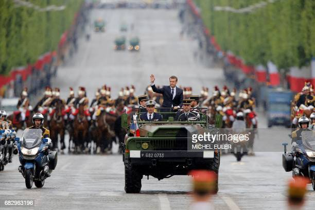 TOPSHOT Newly elected French president Emmanuel Macron waves as he parades in a military car on the Champs Elysees avenue after his formal...