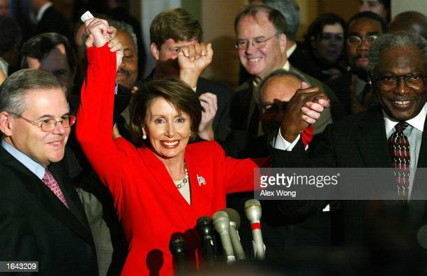 Newly elected House Minority Leader Rep Nancy Pelosi joins hands with fellow Democratic Rep Robert Menendez and Rep James Clyburn to celebrate...