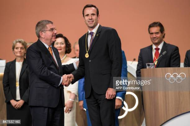 Newly elected International Olympic Committee member and President of the International Rowing Federation French JeanChristophe Rolland shakes hands...